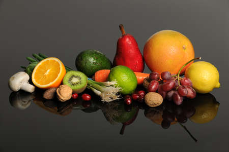 Fresh fruits, nuts, and vegetables on reflective table photo