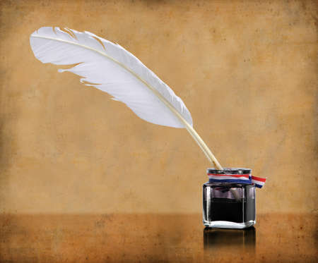 writing desk: Vintage writing quill and inkwell over grunge background Stock Photo