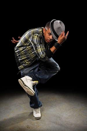 African American hip hop dancer performing over dark background with spotlight