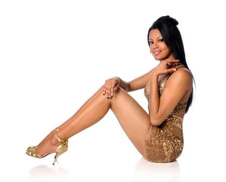 tacones negros: Retrato de la hermosa mujer afroamericana en el vestido dorado aislada sobre fondo blanco