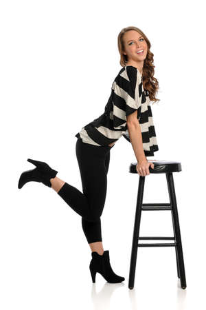 stool: Portrait of beautiful young woman leaning on stool isolated over white background Stock Photo