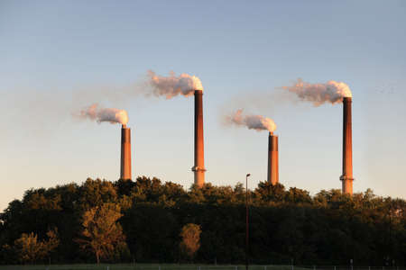 hazardous: Industrial smokestacks blowing smoke at sunset