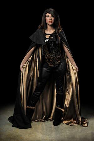 Vrouwelijke vampier staande over donkere achtergrond met schijnwerpers