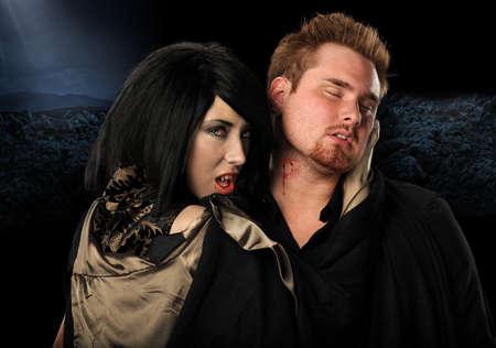 biting: Vampire woman biting man on the neck
