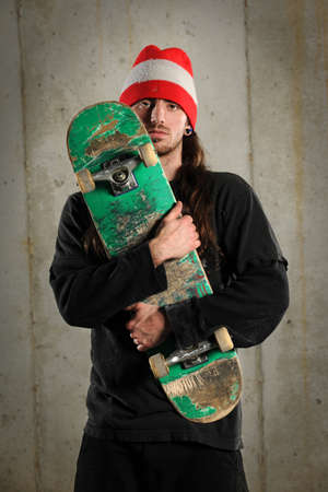Young man holding skateboard over grunge concrete background photo