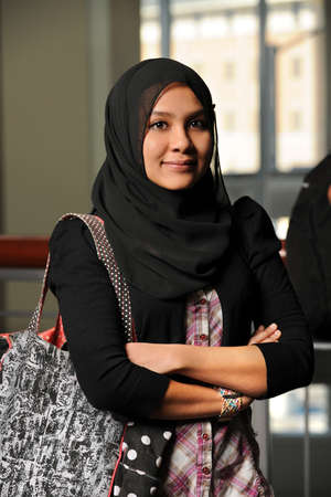Portrait of young Muslim woman with arms crossed photo