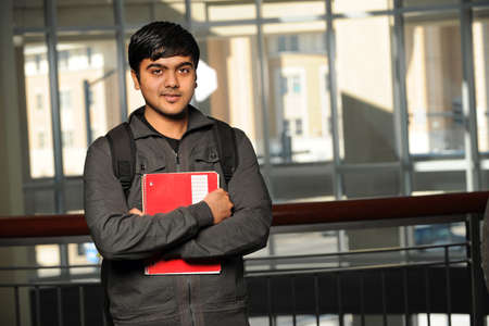 Portrait of young Indian student with school backpack holding notebook inside school building photo