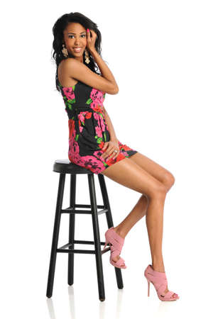stool: Beautiful African American woman sitting on stool isolated over white background Stock Photo