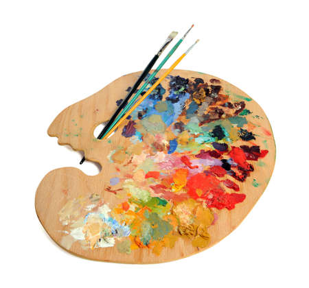 Artist palette with paintbrushes over white background