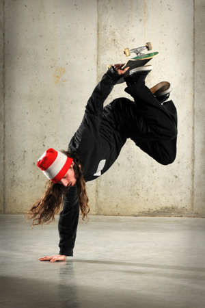 Young man with skateboard performing handstand trick