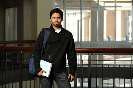 Portrait of young Indian student holding book inside building photo