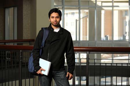 Portret van jonge Indische student die boek in het opbouwen van Stockfoto - 15122650