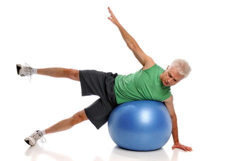Mature man working out with fitness ball isolated over white background photo
