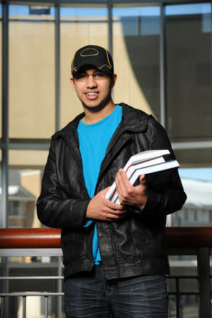 Young Indian student holding books indoors photo
