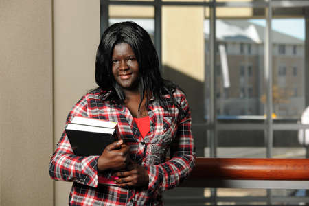 Portrait of african student holding books indoors photo