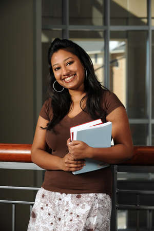 indian student: Portrait of Indian student smiling indoors Stock Photo