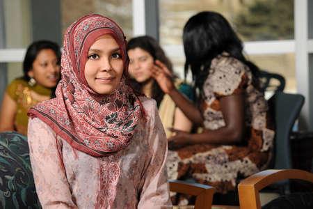 diversidad: Mujer isl�mica joven con el grupo diverso de estudiantes vestidos con ropa tradicional dentro de �mbito escolar