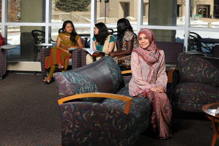 Diverse group of female students dressed in traditional clothing inside school setting photo