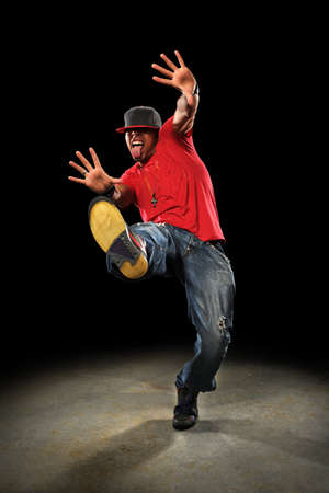 African american hip hop dancer performing over dark background with spotlight Фото со стока