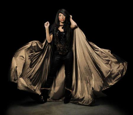 demoniacal: Female vampire with cloak over dark background