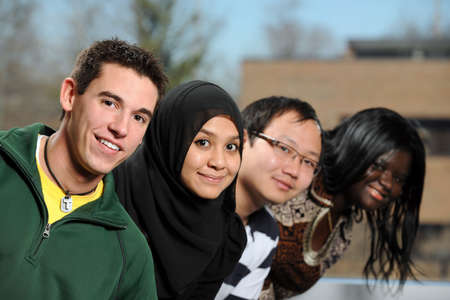 Diverse group of students smiling with selective focus on foreground person photo