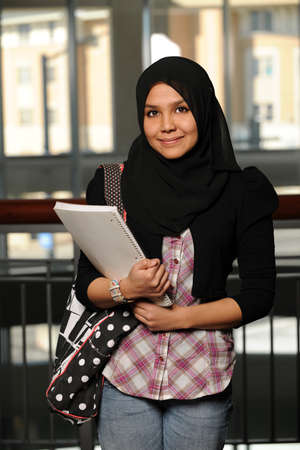 Portrait of Islamic student smiling indoors