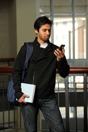 sms: Portrait of young Indian student using cell phone indoors Stock Photo