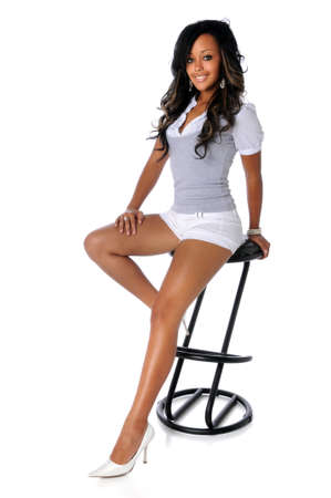 stool: Portrait of beautiful African American woman sitting on stool isolated over white background Stock Photo