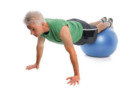Mature man using fitness ball isolated over white background