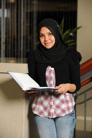 Portrait of beautiful Muslim female student holding open book photo