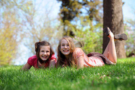 Portrait of young girls resting on grass during sunny spring day photo