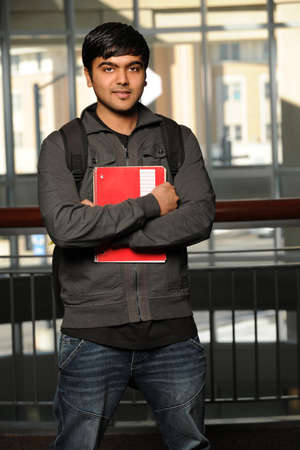 Young Indian student holding notebook photo
