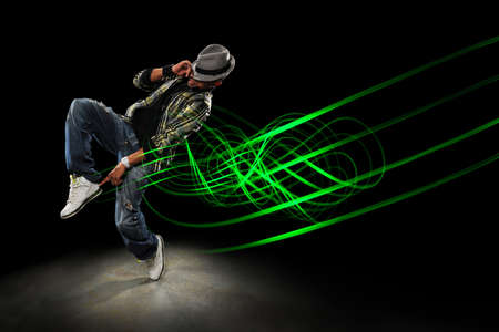 hip hop dancing: African American hip hip dancer with waves of light painting over dark  background Stock Photo