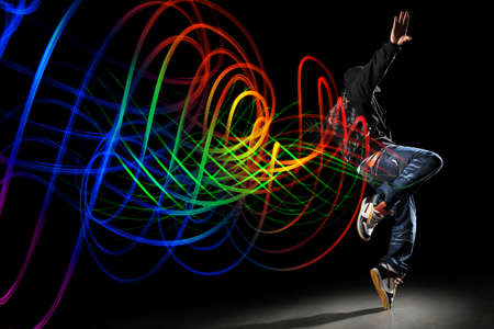 African American hip hip dancer with waves of light painting over dark  background 免版税图像