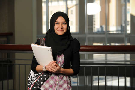Portrait of Islamic young woman holding books indoors photo