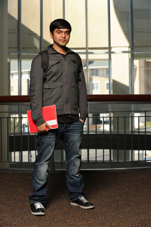 Portrait of Indian student holding notebook indoors photo