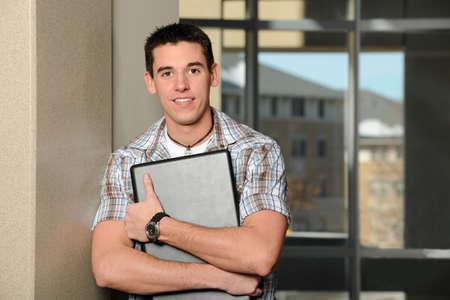 Student holding laptop inside building Stok Fotoğraf
