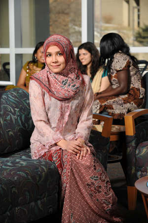 Portrait of young Muslim woman in traditional clothes with others in background