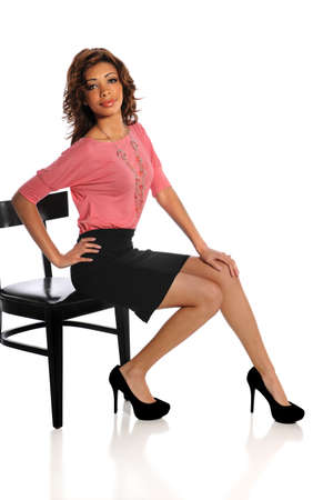 Beautiful African American woman sitting on black chair isolated over white background photo