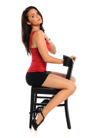 Portrait of beautiful young woman seating on chair isolated over white background Stock Photo