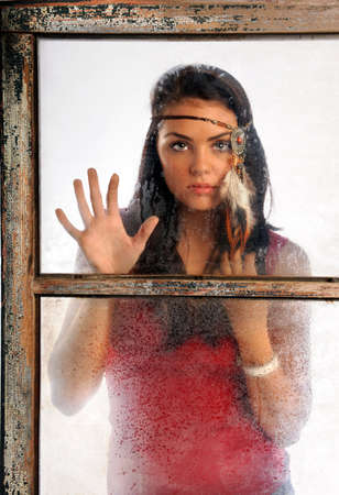 Portrait of beautiful young woman wearing feather headband looking through old window photo