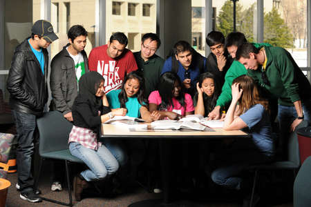 Diverse group of students gather at table interacting