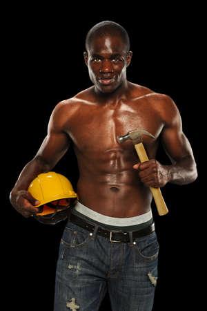 sudando: Hombre afroamericano que sostiene sombrero duro y martillo aislados sobre fondo negro