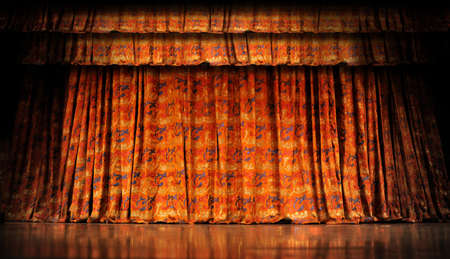 Orange stage curtains with reflection on wood floor photo