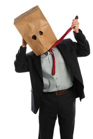 avergonzado: Retrato de hombre de negocios con bolsa de papel en la cabeza tirando empate aislado sobre fondo blanco Foto de archivo