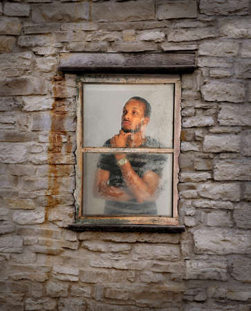 man looking out: African American young man looking out of window during rain