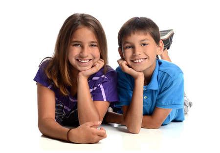 白い背景で隔離の床の上に敷設の女の子と男の子の兄弟
