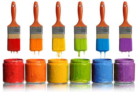 Penselen druipende verf van verschillende kleuren in containers Stockfoto