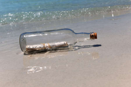 with reflection: Message in a bottle on sandy shore