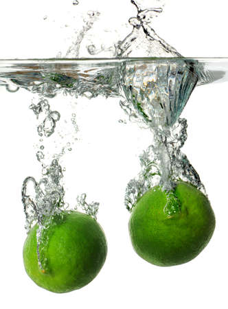 Limes splashing into water over white background